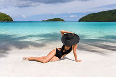 Woman classy beach. Woman on tropical resort beach in elegant black wide brim hat in caribbean exotic luxury island