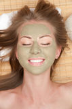 Woman with clay facial mask Stock Photos