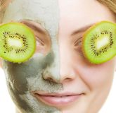 Woman in clay facial mask covering eyes with kiwi Stock Photo
