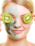Woman in clay facial mask covering eyes with kiwi Stock Images