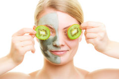 Woman in clay facial mask covering eyes with kiwi Stock Photography