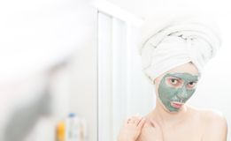 Woman with clay facial mask looking in mirror. Stock Photos