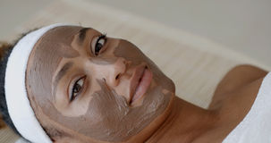 Woman With Clay Facial Mask In Spa. Portrait of girl with a band on her head applying facial mask Stock Photography