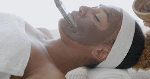 Woman With Clay Facial Mask In Spa Royalty Free Stock Image