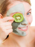 Woman in clay mask on face covering eye with kiwi Royalty Free Stock Photo
