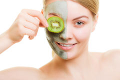 Woman in clay mask on face covering eye with kiwi Stock Images
