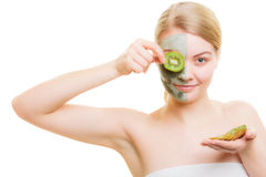 Woman in clay mask on face covering eye with kiwi Stock Photography