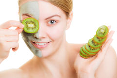 Woman in clay mask on face covering eye with kiwi Stock Image