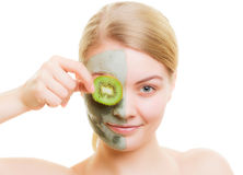Woman in clay mask on face covering eye with kiwi Royalty Free Stock Photos