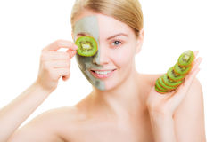 Woman in clay mask on face covering eye with kiwi Stock Photos