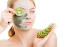Woman in clay mask on face covering eye with kiwi Royalty Free Stock Images