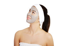 Woman with clay mask on face looking up. Stock Image