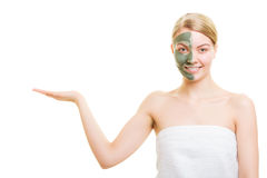 Woman in clay mud mask on face holds open palm Stock Photography