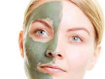 Woman in clay mud mask on face isolated on white. Stock Photography