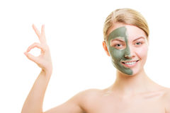 Woman in clay mud mask on face isolated on white. Royalty Free Stock Photos