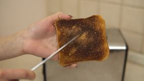 Woman clean the ashes with a burnt toast with a knife. Toasted bread in a toaster