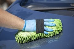 Woman clean blue car in glowes, green sponge in hand stock images
