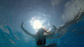 Woman in clean blue pool swims underwater with open eyes in vibrant environment on background bubbles. Girl in clean blue pool swims underwater with open eyes in stock footage