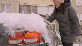 . Woman clean car snow for concept design. Cleaning concept. Winter snow season. Snow covered car. Winter snow season. Woman cleaning snow from car windshield stock video footage
