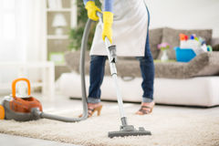 Woman clean carpet with vacuum cleaner Stock Photos