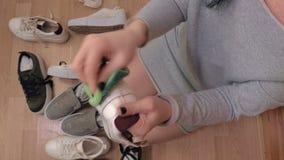 Woman clean dirty sneakers. In room stock video