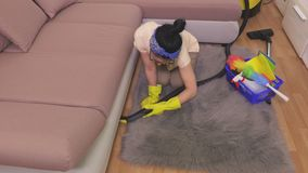 Woman clean edge of sofa with vacuum cleaner. In room stock footage