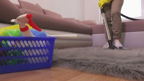 Woman clean faux fur rug with vacuum cleaner. In room stock video footage