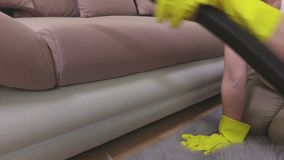 Woman clean front side of sofa with vacuum cleaner. In room stock footage