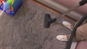 Woman clean rug with vacuum cleaner. In room stock footage
