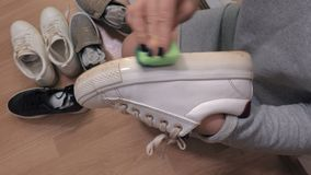Woman clean sole of white sneakers. In room stock video