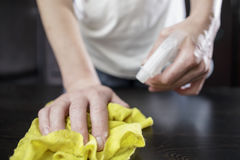 Woman cleaner wipes the table with the help of a yellow cloth Stock Photos