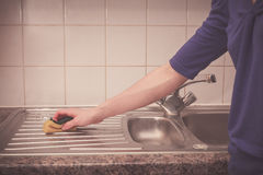 Woman cleaning around the kitchen sink Royalty Free Stock Photos