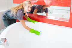 Woman cleaning bath Stock Images