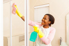 Woman cleaning bathroom. Happy african american woman cleaning bathroom Stock Photography