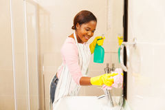 Woman cleaning bathroom mirror. Smiling young woman cleaning bathroom mirror at home royalty free stock photos