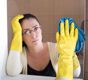 Woman cleaning bathroom mirror Stock Photo