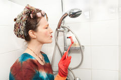 Woman cleaning bathroom shower Stock Image