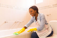 Woman cleaning bathtub. Beautiful young african woman cleaning bathtub with a cloth Stock Image