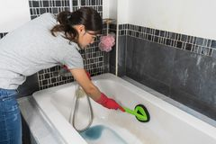 Woman cleaning bathtub with brush stock image