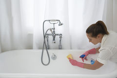 Woman Cleaning Bathtub. Young woman cleaning up the bathtub with sponge and cleaner at home Stock Photography