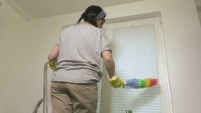 Woman cleaning blinds in kitchen