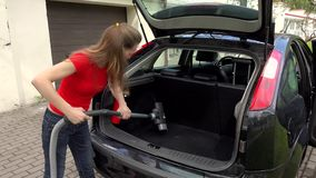 Woman Cleaning Boot Interior Of Car Using Vacuum Cleaner. stock video