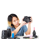 Woman cleaning a camera with cloth and photography equipment Royalty Free Stock Images
