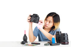 Woman cleaning a camera with cloth and photography equipment on table royalty free stock photography