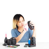 Woman cleaning a camera with cloth and photography equipment on table. Stock Image