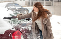 Woman cleaning car at blizzard Royalty Free Stock Photography