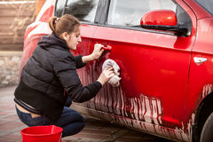 Woman cleaning car door from mud and dirt Stock Images