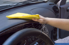 Woman cleaning the car interior. With yellow cloth Stock Photo