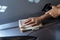 Woman cleaning car with microfiber cloth and clean spray. On dark background Royalty Free Stock Photos