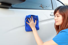 A woman cleaning car with microfiber cloth Royalty Free Stock Image